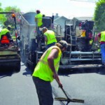 Public works employees in Des Moines, Iowa, pave asphalt.