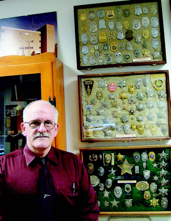 Lain's collection of badges represents various Indiana cities and towns, including Lake County, middle frame, and Porter County, bottom frame. (Photo by Dee Dunheim)