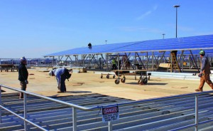 Workers continue to place photovoltaic modules over one of the tanks at the Camden wastewater treatment plant while others secure wood over metal supports so work can be completed safely. (Provided by groSolar)