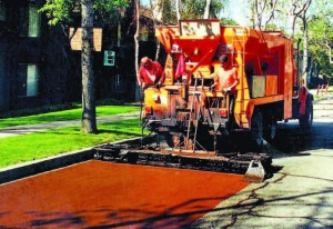 Slurry Seal coating and micro-surfacing have been touted as versatile and low-cost applications that can extend the life of city streets by five to seven years. Both petroleum-based emulsion products are mixed with a fine chip aggregate and spread in thin layers to fill cracks and ruts. (Photo provided)