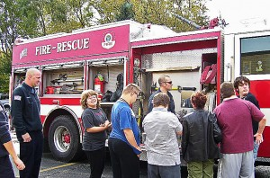 During an autism training session at the Mundelein, Ill., Fire Department, the company takes an engine, an ambulance and its parade vehicle and opens the doors, allowing the kids to walk through, explore and familiarize themselves with the vehicles on their terms. From left are firefighters/paramedics Brad Sashko and Jackie Ulrich with session participants. (Photo provided)
