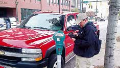 A parking ambassador writes a parking ticket prior to the installation of solar-powered meters in several locations around Chattanooga, Tenn. (Photo provided)