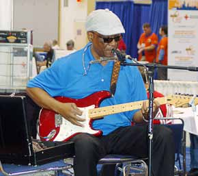 A harmonica blues player entertains for APWA attendees transitioning from the exposition hall to session classrooms at Lakeside Center, McCormick Place, Chicago. (Photo by Jodi Magallanes)