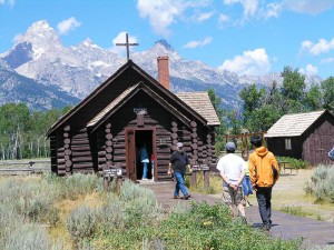 Visitors approach the Chapel of Transfiguration at Grand Teton National Park, Wyoming. Fewer employees at national parks have meant longer lines at entry stations, reductions in the daily hours of operation and other cutbacks. (Photo courtesy National Park Service)