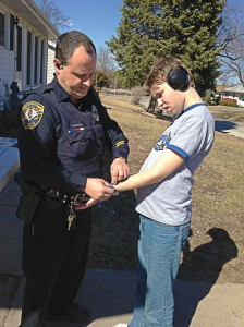 Quincy, Ill., Officer Tom Liesen fastens a tracking device to the wrist of a 19-year-old boy with autism. (Photo provided)