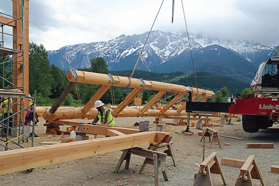 Portion of the barn is moved into place in May after being hand-hewn by members of the Timber Framers Guild, local craftsmen and apprentices. The nontraditional building method saved the town thousands in construction costs and gave residents a large measure of pride in the structure. (Photo provided)