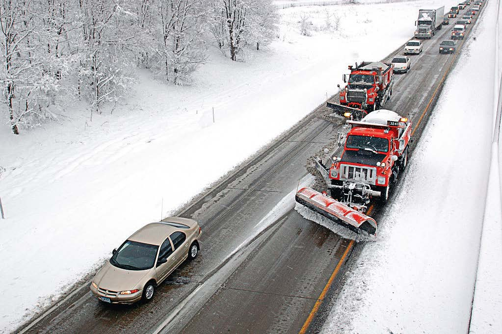 Minnesota Department of Transportation snowplow trucks clear a stretch of road with a string of motorists behind them. Many states focus on educating the public early in the season on safe winter driving habits, including about how to drive when near snowplows. (Photo provided)