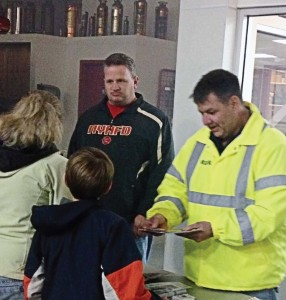 Captain Kevin Reather, left, and Assistant Chief Mark Thomas, both of the Norwood Young America, Minn., Fire Department, discuss fire safety and prevention with members of the public