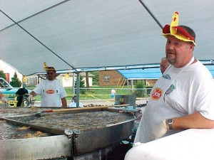 Volunteers man a giant deep fryer at the World Chicken Festival in London, Ky.