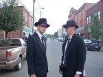 "Two ""Men in Black"" visitors to the Mothman Festival in Point Pleasant, W.Va., last year came prepared to eradicate the fi ctional threat celebrated by the town each September. (Photo provided)"