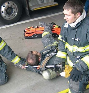 Placing a halligan or axe handle through the SCBA shoulder straps is fast and allows two firefighters to spread out so they can drag the down firefighter without bumping into each other, making the drag more effective.