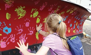 Many hands make light work of painting a snowplow in Lake in the Hills during a public open house last year. (Photo provided)
