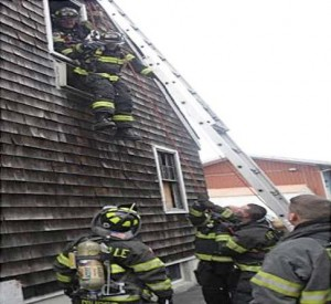 NEXT: The outside team uses the ground ladder like a brake bar rack to lower the firefighter to the ground (Photo provided).