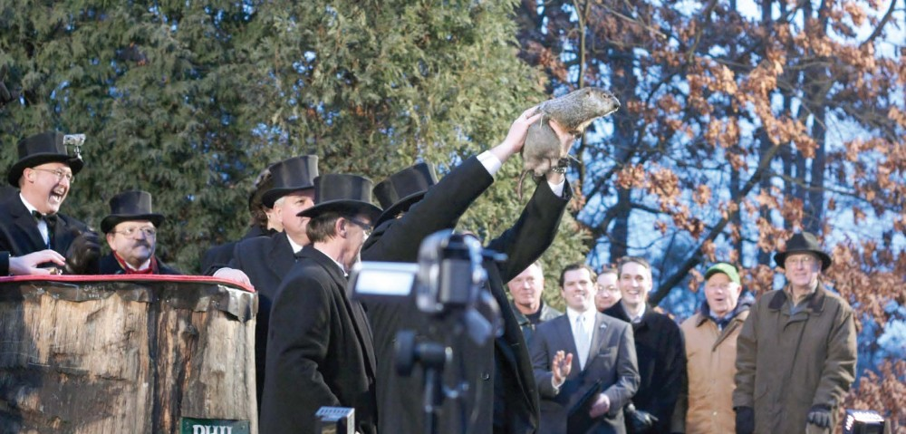 Punxsutawney Phil is held aloft and presented to the crowd by handler John Griffiths just before Punxsutawney's annual Groundhog Day prediction.