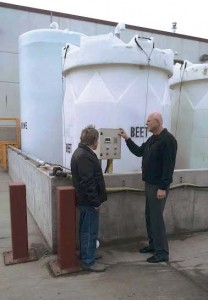 Reeder, right, speaks with an employee in front of the Council Bluffs anti-icing/deicing storage tanks. The beet tank is 6,000 gallons in size; the two brine tanks are 10,000 and 7,500 gallons; and the calcium is 6,000 gallons. (Photo provided)