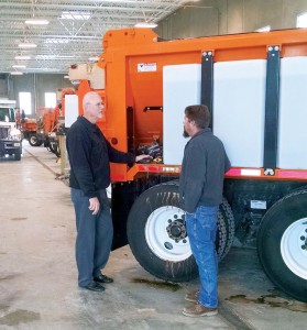 This Council Bluffs, Iowa plow truck is outfitted with solution tanks on the side. Public Works Director Greg Reeder's hand is on the hoses that connect the tanks to the sprayer as he gives instructions to an employee. (Photo provided)