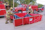 Local firefighters take advantage of Husky Portable Containment's Easy Lift Handles for portable water tanks. (Photo provided)
