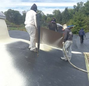 Pictured is a spray polyurethane foam roofing system being applied over a primed commercial roof. (Photo provided by SPFA)