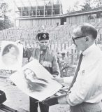 "Kermit Hunter, right, author of ""The McIntosh Trail,"" looks at artistrenditions of William and Susanna McIntosh with Chief W.E. ""Dode"" McIntosh, their great-great-grandson. In the background, workers finish up construction of the Peachtree City Amphitheater, which hosted Hunter's play as its inaugural production. (Photo by Glen Allen)"
