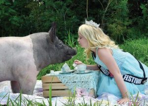 Little Miss World Festival Queen Lucy Kuepler hosts a tea party for her porky guest. (Photo provided by Larry Flannery)