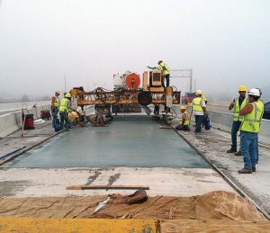 Contractors hand-level the concrete as they complete the bridge deck overlay on the I-69/SR 1 project in Fort Wayne, Ind. (Photo provided by INDOT)