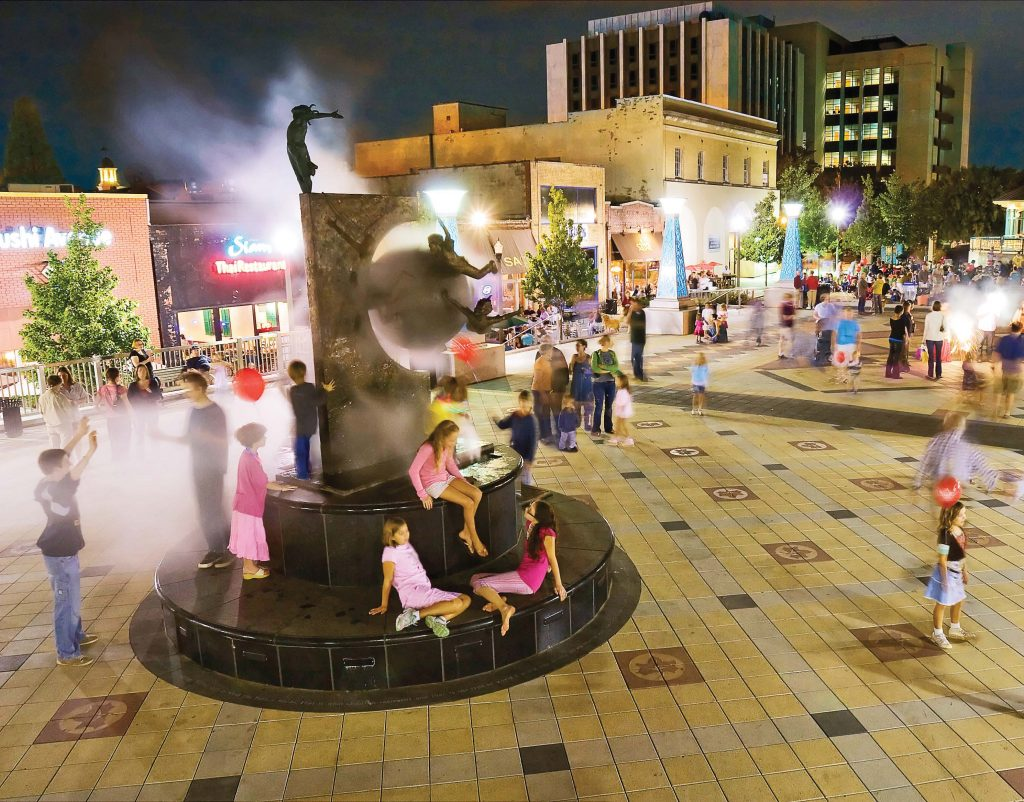 People gather at Decatur's Plaza Fountain. The city's efforts to practice environmental sustainability have attracted people, businesses and visitors. It's become a real marketing and economic tool for the city. (Photo provided)