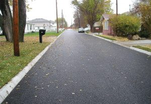 "This ""after"" photo shows a recently installed porous asphalt road in the East Manawa neighborhood of Council Bluffs. The pores in the asphalt are visible in the photo. Not only does the porous asphalt help with drainage, it's been making cleaning the streets of ice and snow easier, plus it improves the overall look of the neighborhood. (Photo provided)"