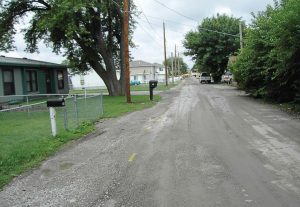 "This ""before"" photo shows a road in the East Manawa neighborhood with gravel runoff and puddling along the road. These types of issues are common in this area and created the need for the city of Council Bluffs to look at some creative ways to deal with them — like porous asphalt. (Photo provided)"