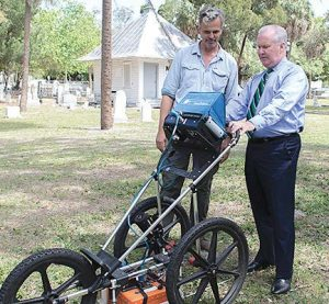 From left, Thomas Pluckhahn, associate professor and archaeologist at the University of South Florida, and Tampa Mayor Bob Buckhorn test out a ground-penetrating radar unit in Oaklawn Cemetery. (Photo provided)