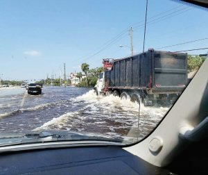 Drivers travel through water left by Hurricane Irma in the Bonita Springs, Fla., area. Floodwaters can contain sewage making them dangerous for people wading through them. (Photo provided)