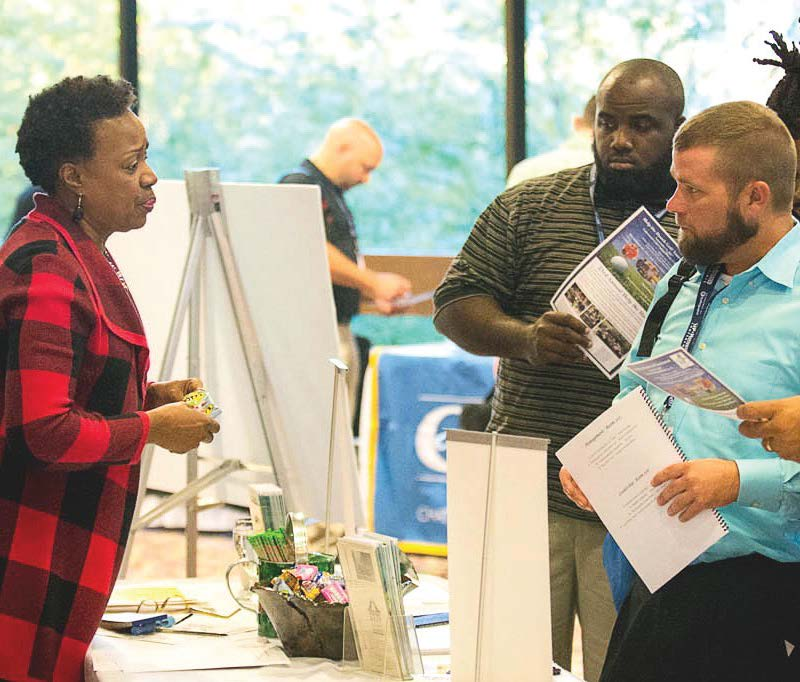 Employees talk with Keep Columbus Beautiful Executive Director Gloria Weston Smart about a program to reduce litter at an Up and Motivated conference