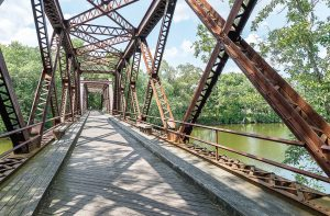 Many cities and towns are turning abandoned rail lines into community assets in the form of rail trails. Pictured is the Springtown Bridge, which crosses over the Wallkill River near New Platz, N.Y. It is a part of the Wallkill Valley Rail Trail. (Shutterstock. com)