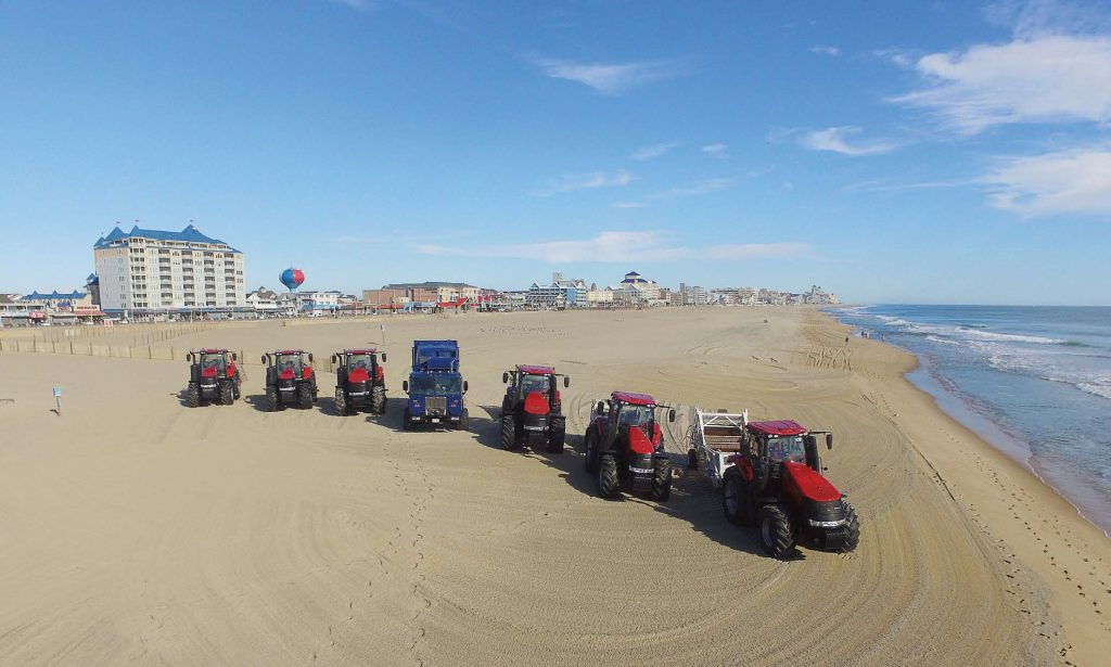Red beach cleaners and a blue beach trash truck comb a Ocean City, Md., beach. The city has a fuel depot with four underground storage tanks and several contingency plans ready should a disaster — whether man-made or natural — disrupt fuel from reaching the island. (Photo provided)