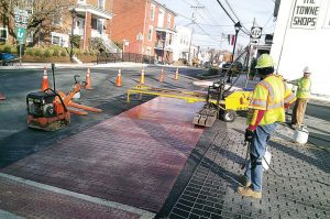 Workers give the appearance of brick to a crosswalk in downtown Stanardsville, matching the surrounding buildings' historic brick charm. Grants have helped move the streetscape forward. (Photo provided)