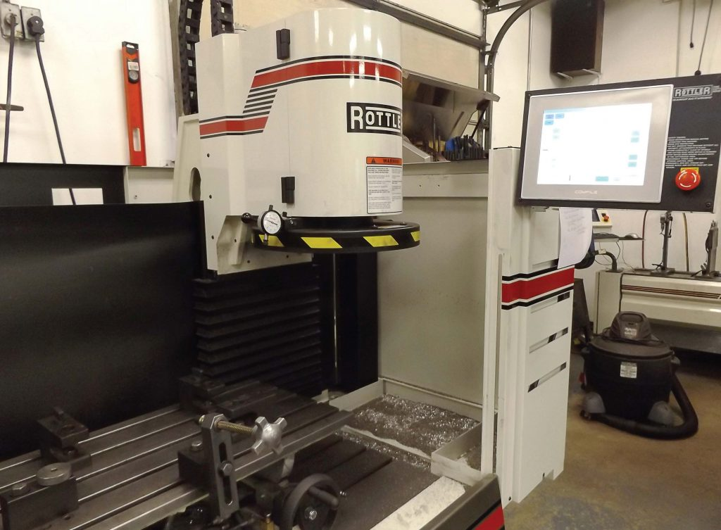 This CNC resurfacing machine can extend the life of vehicles for cities and towns. The engine part is clamped down and the diamond cutting edge travels above it while the touch screen, where the machine is programmed, extends out to the side. (Photo by Denise Fedorow)