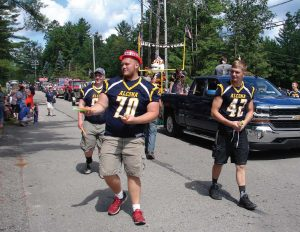 Alcona Community Schools football players hand out frozen treats to parade spectators. (Photo provided)
