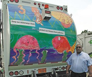 Delbert Bryant poses with one of Greenville's sanitation trucks, which was part of Greenville's student art contest. (Photo provided)