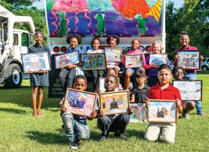 "Winners of the ""Keep the Green in Greenville"" poster competition for young pupils in Pitt County pose with their paintings. Paintings were then enlarged and placed on sanitation trucks to increase awareness of environmental concerns. (Photo provided)"
