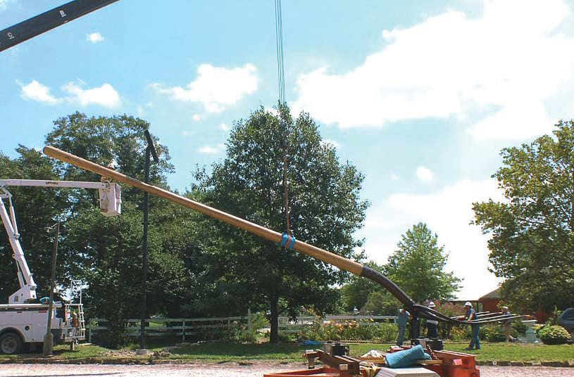 Workers from Bolin Enterprises are dwarfed by the 60-foot pitchfork as they install it on a farm property just outside of town. (Photo provided)