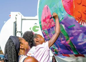 A young artist signs her painting on the back of a Greenville, N.C., sanitation truck. (Photo provided)