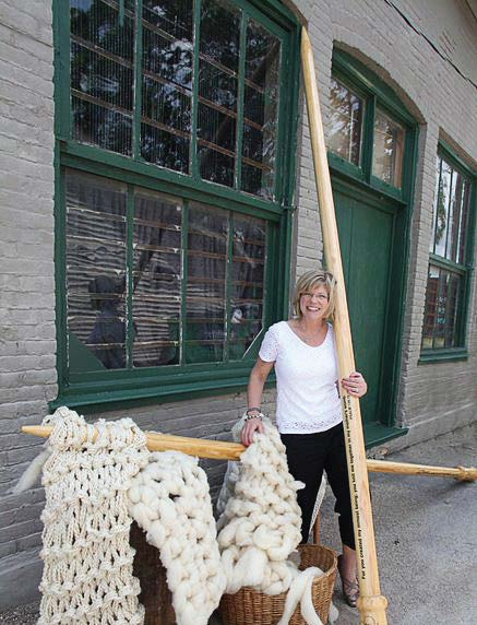 Jeanette Huisinga, owner of The Yarn Studio, stands with the world's largest knitting needles and the stitches she muscled together at the local elementary school to qualify for the Guinness World Records. (Photo provided)