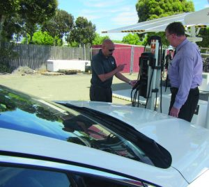 From left, Jason Chin, Oakland's fleet compliance coordinator, and Richard Battersby, interim assistant director of Oakland's bureau of infrastructure and operations, check out one of the EV ARC self-contained, solar-powered Level 2 charging stations. Electric cars charged at it will be using 100 percent renewable fuel. (Photo provided)