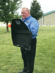 Keith Brown holds his invention, Attack Mats, which is a floor mat that doubles as a light-weight ballistic shield. Still functional as floor mat, it is easily accessible should an officer need it while responding to a call. (Photo provided)