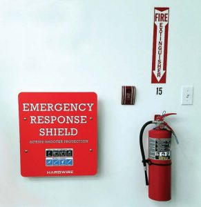 "Much like a fire extinguisher, an emergency response shield can be placed in a building in case of an active shooter. They can be labeled as such, above right, or concealed as artwork or an advertisement, like this ""Seacrets Hand-Crafted Gin"" sign, above left. (Photo provided by Hardwire)"