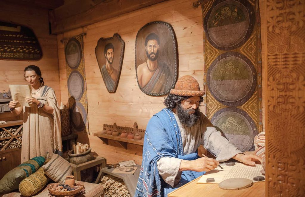 In one of several dioramas in the ark, Noah records an entry in his captain's log as his wife reads a parchment.