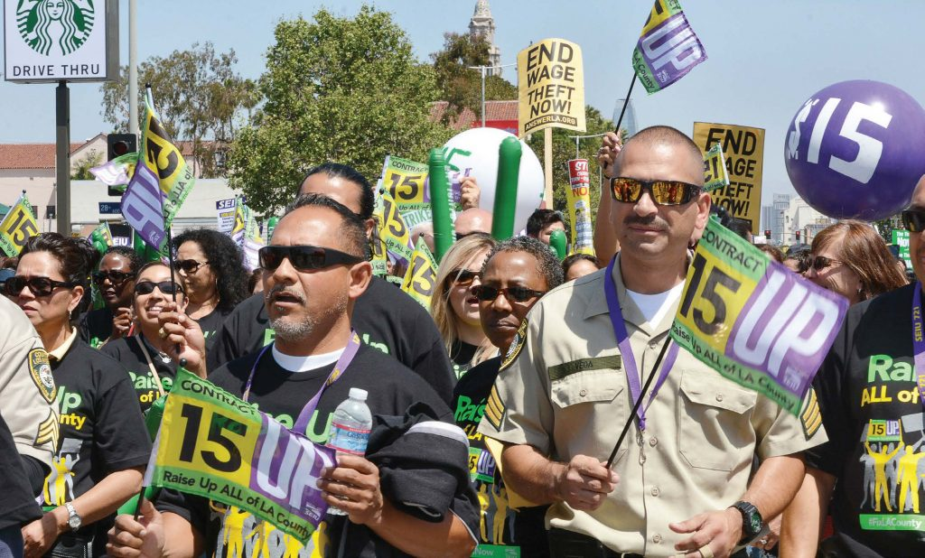 Protestors hold signs and flags advocating raising the minimum wage during a demonstration in Los Angeles on April 15, 2015. The state of California has 22 communities that have enacted minimum wage ordinances, the majority of which are on a path to $15 per hour. (Dan Holm/Shutterstock.com)