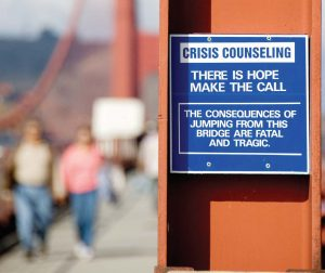 A suicide prevention notice posted on the Golden Gate Bridge. In addition to fencing, suicidal hotline signage can make a difference in suicide prevention. (Shutterstock.com)