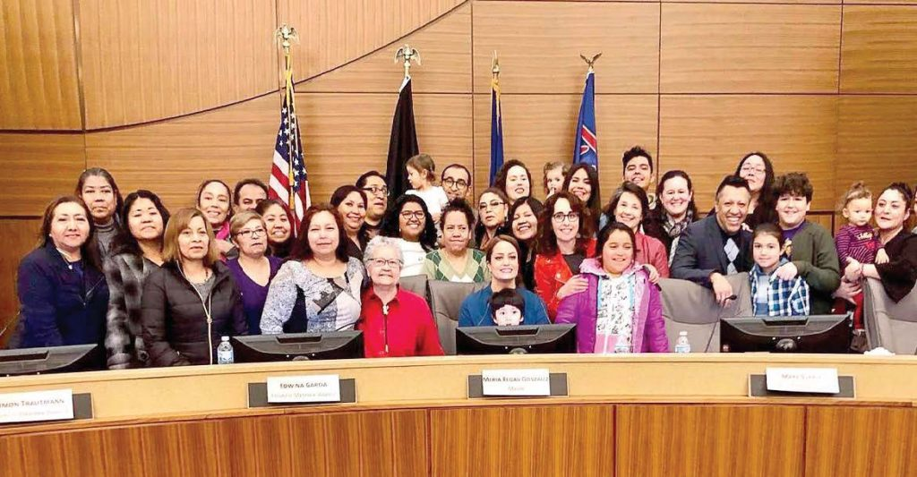 Marie Regan Gonzalez, the new mayor of Richfield, Minn., poses with members of the community as she sits in her new chair. She is the first Latina mayor in Minnesota history. (Photo provided)