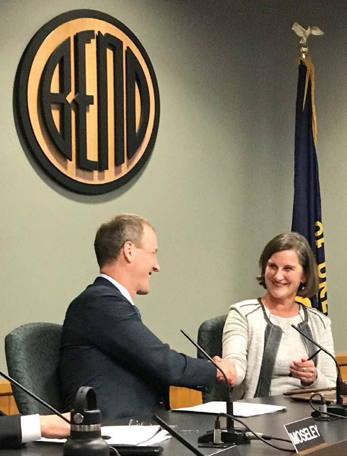 Bend, Ore., Mayor Sally Russell shakes hands with City Councilor Bill Moseley. (Photo provided)